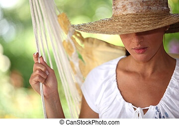 Woman with straw hat sat in a hammock