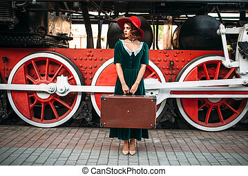 Woman with suitcase against steam locomotive - Woman in red...