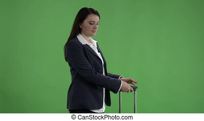 Woman with suitcase checking schedule on departure board against green screen