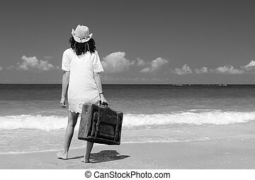 woman with suitcase on the beach