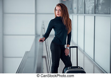 Woman with suitcase posing on the glassed balcony.
