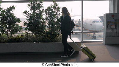 Woman with suitcase talking on phone and walking in airport terminal