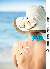 Woman With Sun Drawn From Sunscreen On Back - Rear view of...