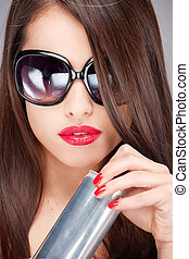 woman with sun glasses holding can