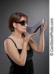 woman with sunglasses kissing shoe