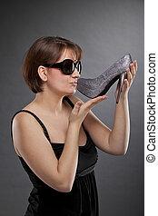 woman with sunglasses kissing shoe - A low key studio shot ...