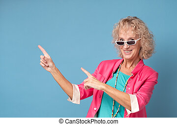 woman with sunglasses smiling cheerfully and pointing with ...