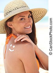 woman with sunscreen on the beach wearing a hat