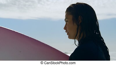 Woman with surfboard standing on the Beach 4k