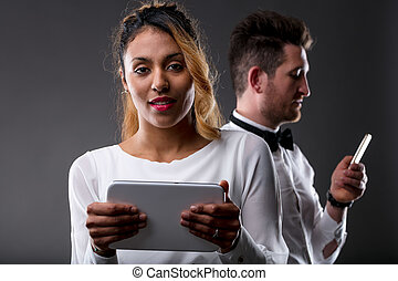woman with tablet and man with mobile phone