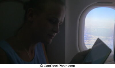 Woman with Tablet by the Plane Window