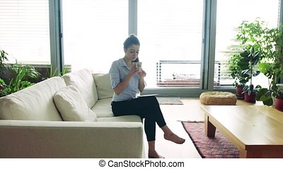 Woman with tablet in living room. Smart home. - A woman with...