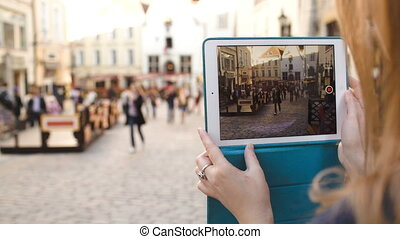 Woman with tablet making video of street in Tallin and then watching it
