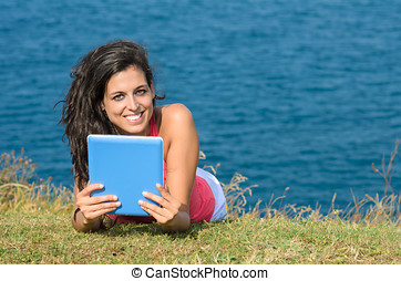 Woman with tablet on vacations in summer