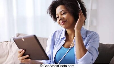 woman with tablet pc and headphones at home - music,...