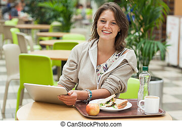 Woman with tablet PC and meal in cafeteria