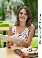 Woman with tablet PC and meal in the cafeteria