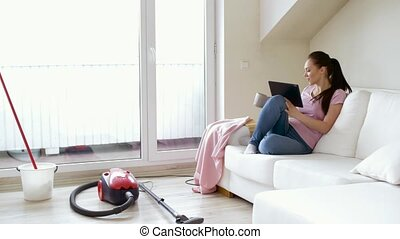 woman with tablet pc and tea after cleaning home - cleaning,...