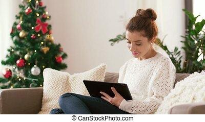 woman with tablet pc at home on christmas - christmas,...