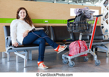Woman with tablet pc charging devices in airport lounge with luggage hand-cart