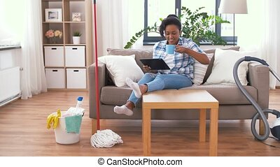 woman with tablet pc resting after home cleaning - household...