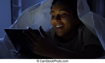 woman with tablet pc under blanket in bed at night