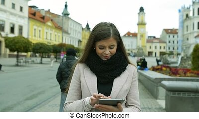 Woman with tablet walking outdoors in old town