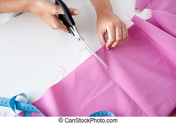 woman with tailor scissors cutting out fabric
