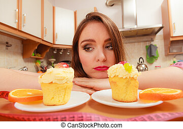 Woman with tape measure and cake. Diet dilemma.