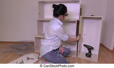 Woman with tape measure near furniture