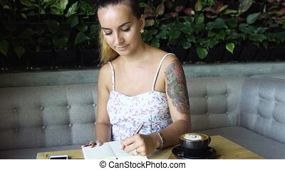 Woman with tattoo studying and writing in notebook. Female sitting at table in cosy cafe.