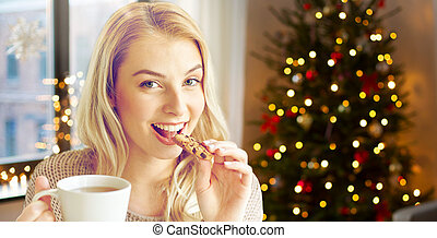 woman with tea eating cookie on christmas at home
