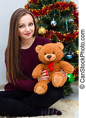 Woman with teddy bear near the Christmas tree