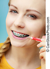 Woman with teeth braces using interdental brush - Dentist...