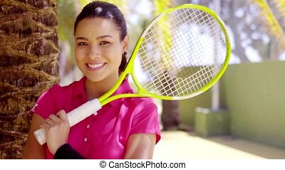 Woman with tennis racket beside palm tree