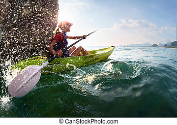 Woman with the kayak - Young lady paddling hard the kayak...