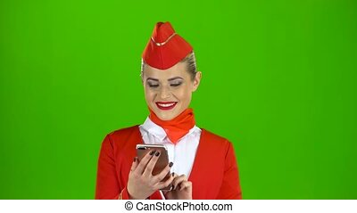 Woman with the phone and writes a message . Green screen