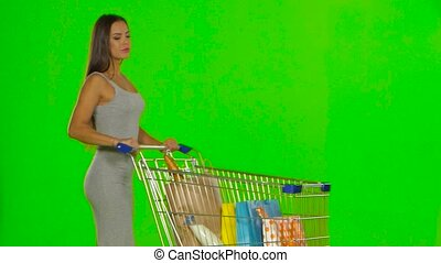 Woman with the trolley makes a turn and stops. Green screen