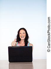 Woman with thumbs up using her laptop