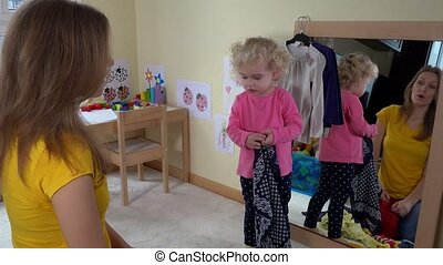 Woman with toddler girl have fun at home