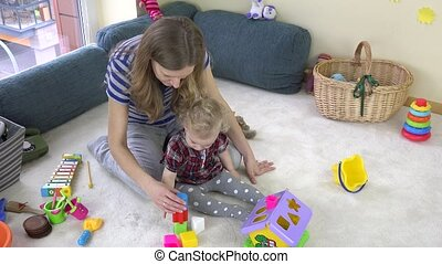 Woman with toddler girl try to make toy brick tower.