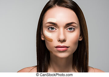 woman with tonal foundation on face isolated on grey