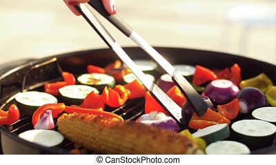 woman with tongs cooking vegetables on bbq grill - food,...