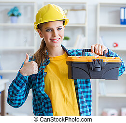 Woman with toolkit in workshop - The woman with toolkit in...