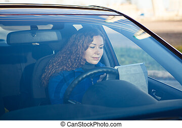 Woman with touchpad sitting in car on driver seat