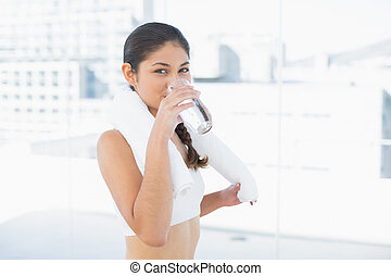 Woman with towel around neck drinking water in fitness studio