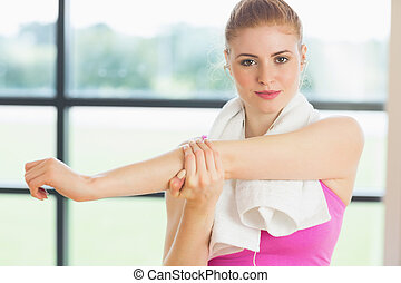 Woman with towel around neck stretching hand in fitness studio