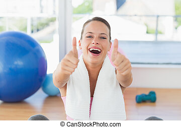 Woman with towel gesturing thumbs up in gym