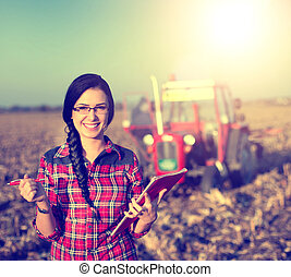 Woman with tractor on the field - Beautiful young woman...