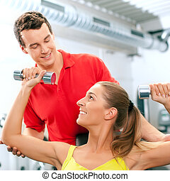 Woman with trainer and dumbbells in gym